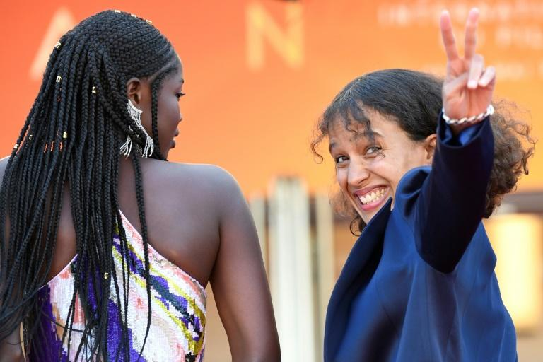 "French actress and film director Mati Diop (R) flashes the victory sign as she arrives with Senegalese actress Mama Sane for the screening of the film ""Atlantics (Atlantique)"" at the 72nd edition of the Cannes Film Festival"