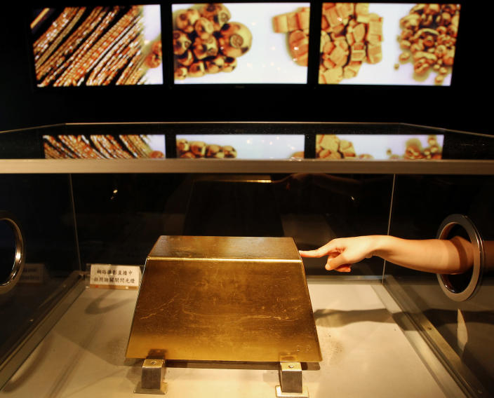 A visitor touches a 220kg gold bar at Jinguashi Gold Ecological Park, Taiwan. Photo: Pichi Chuang/Reuters