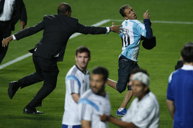 In this Wednesday, June 11, 2014 photo, a security guard fails to stop a fan, wearing an Argentine soccer jersey,who storms the pitch past Lionel Messi, center left, and other players, at the end of a training session at Independencia Stadium in Belo Horizonte, Brazil. (AP Photo/Victor R. Caivano)