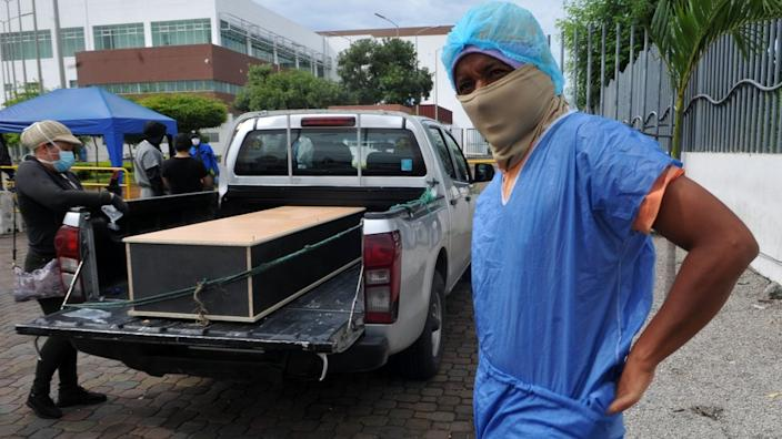A man in Guayaquil wears protective kit so that he can enter a morgue and identify a relative who died of Covid-19