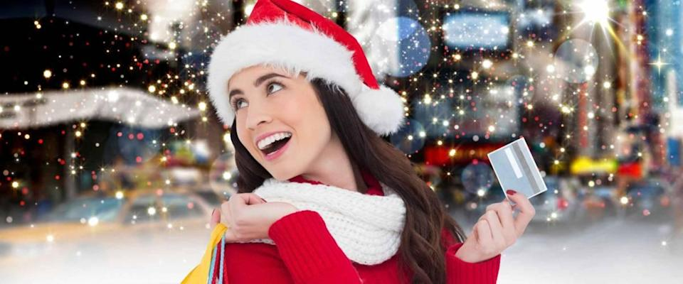 Cheerful woman in santa costume holding shopping bag and credit card against digitally generated sparkling background