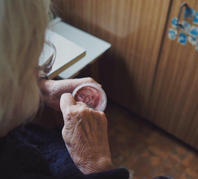 Old woman in care home eating a yoghurt