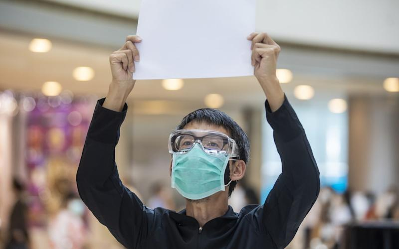 A protester holds up a blank sheet of paper after the introduction of a crackdown on freedom of speech - Bloomberg