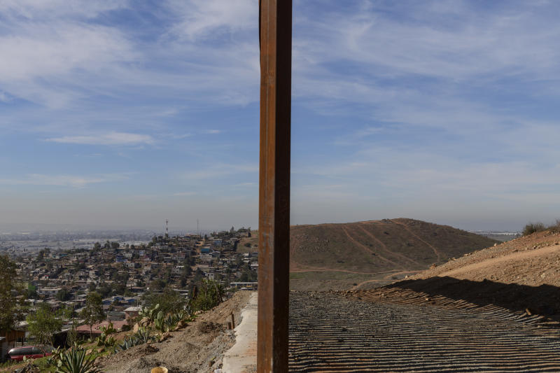 Tijuana, Mexico, left, and San Diego, Calif, right, are seen separated by the U.S. border fence, on Saturday, Dec. 22, 2018. The Trump administration's decision to make asylum seekers wait in Mexico while their cases wind through clogged U.S. courts was announced with crucial details still unknown — a move that creates uncertainty along the border and possibly an incentive for people to cross illegally before the change take effect. (AP Photo/Daniel Ochoa de Olza)