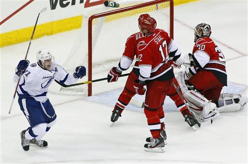 Tampa Bay Lightning's Steven Stamkos (91) celebrates his game-winning overtime goal in front of Carolina Hurricanes' Eric Staal (12), Tim Gleason (6) and goalie Cam Ward (30) during an NHL hockey game in Raleigh, N.C., Saturday, March 3, 2012. Tampa Bay won 4-3.  (AP Photo/Karl B DeBlaker)