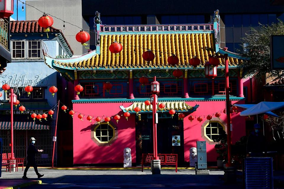 A pedestrian wearing a facemask walks though Chinatown Central Plaza on the first day of the Lunar New Year of the Ox in Los Angeles