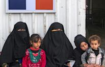 Displaced Syrian woman and children wait at the al-Hol camp in northeastern Syrian