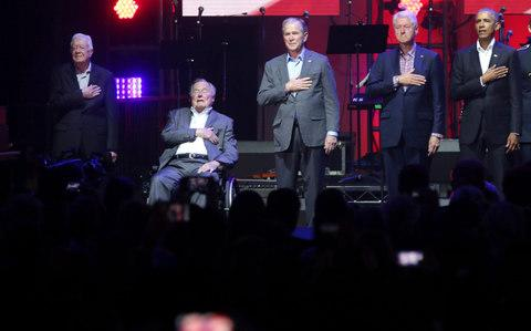 "The five living former presidents appeared together for the first time since 2013 on Saturday at a concert to raise money for victims of devastating hurricanes in Texas, Florida, Puerto Rico and the U.S. Virgin Islands. Democrats Barack Obama, Bill Clinton and Jimmy Carter and Republicans George H.W. and George W. Bush gathered on stage in College Station, Texas, home of Texas A&M University, putting aside politics to try to unite the country after the storms. Texas A&M is home to the presidential library of the elder Bush. At 93, he has a form of Parkinson's disease and appeared in a wheelchair at the event. His wife Barbara and George W. Bush's wife Laura Bush were in the audience. The concert features the country music band Alabama, Rock & Roll Hall of Famer 'Soul Man' Sam Moore, gospel legend Yolanda Adams and Texas musicians Lyle Lovett and Robert Earl Keen. Earlier on Saturday, President Donald Trump recorded a video greeting that avoids his past criticism of the former presidents and called them ""some of America's finest public servants."" ""This wonderful effort reminds us that we truly are one nation under God, all unified by our values and devotion to one another,"" Trump said in the message. The last time the five were together was in 2013, when Obama was still in office, at the dedication of George W. Bush's presidential library in Dallas. At a glance 