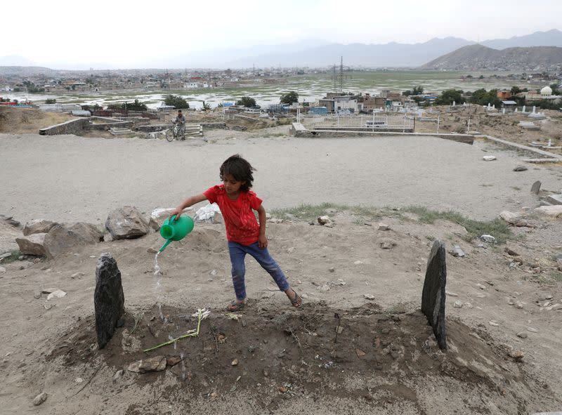 A girl spills water over the grave of twenty-four-year old Fatima Khalil, known as 'Natasha', who was killed in a bomb blast on Saturday, in Kabul