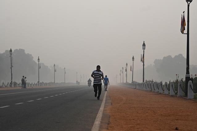 A man jogs along a street under smoggy conditions in New Delhi on Nov. 1, 2019. (Photo: Jewel Samad/AFP via Getty Images)