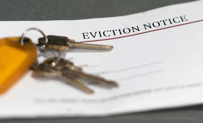 House keys sitting on an eviction notice received in the mail.