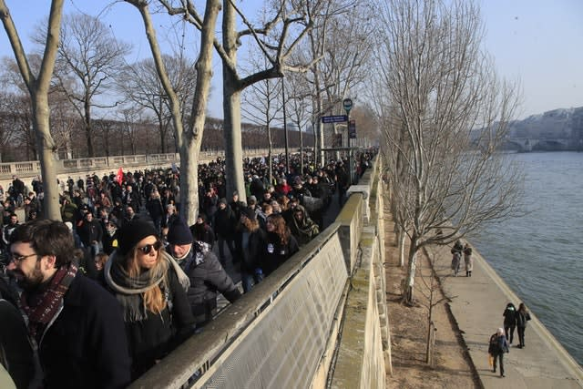 People march along the Seine river during a demonstration in Paris