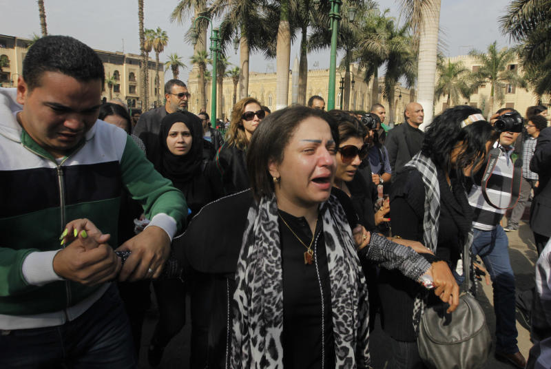 "Zeinab Negm, center, a daughter of Egypt's best known satirical poet, Ahmed Fouad Negm, grieves with others during his funeral outside al-Hussein mosque in Cairo, Egypt, Tuesday, Dec. 3, 2013. Known as the ""poet of the people,"" Negm's use of colloquial Egyptian Arabic endeared him to his countrymen who saw in his verse an unvarnished reflection of how they felt about milestones in their nation's history like the humiliating defeat at the hands of Israel in 1967, the 1979 peace treaty with Israel and the authoritarian rule of Hosni Mubarak. (AP Photo/Amr Nabil)"
