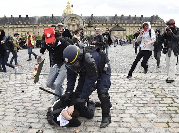 A police officer clashes with a demonstrator near the Invalides during a protest against proposed labour reforms, in Paris on June 14, 2016 (AFP Photo/Dominique Faget)