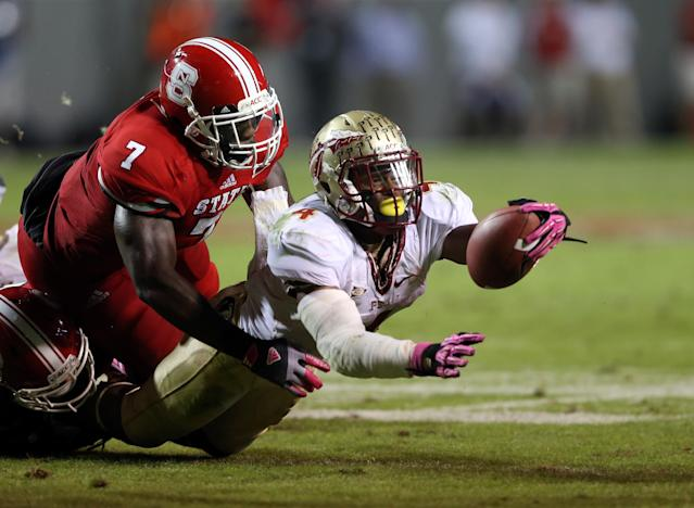RALEIGH, NC - OCTOBER 06: Sterling Lucas #7 of the North Carolina State Wolfpack stops Chris Thompson #4 of the Florida State Seminoles during their game at Carter-Finley Stadium on October 6, 2012 in Raleigh, North Carolina. (Photo by Streeter Lecka/Getty Images)