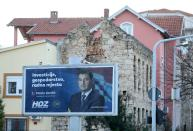 An election sign is seen in front of a house that was destroyed during the 1992-1995 war, in Mostar