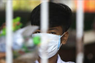 A school student wearing a face-mask, looks on from a class room during a morning class at Santhormok high school, in Phnom Penh, Cambodia, Monday, Nov. 2, 2020. Schools throughout Cambodia reopened Monday for the first time since March but with class sizes and hours limited by coronavirus precautions. (AP Photo/Heng Sinith)