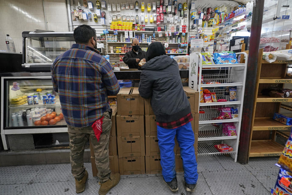 Bodega owner Francisco Marte helps two customers Wednesday, Feb. 10, 2021, at his small grocery store in the Bronx borough of New York. Marte, president of the Bodega and Small Business Group, which represents bodegas in New York, has been lobbying local officials to set aside vaccine appointments for bodega workers, many of whom are unaware they are eligible. He hopes that the recent opening of a large vaccination site at Yankee stadium will make access easier. (AP Photo/Kathy Willens)
