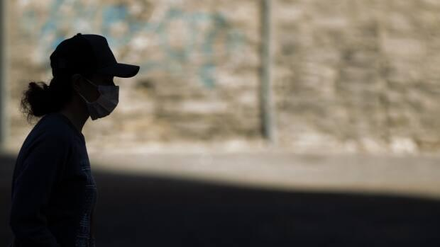 A person wearing a mask is obscured by shadow in Ottawa on April 8, 2021. (Andrew Lee/CBC - image credit)