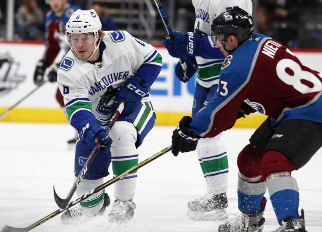 Vancouver Canucks right wing Brock Boeser, left, shoots the puck past Colorado Avalanche left wing Matt Nieto in the second period of an NHL hockey game Monday, Feb. 26, 2018, in Denver. (AP Photo/David Zalubowski)
