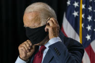 Democratic presidential candidate former Vice President Joe Biden joined by his running mate Sen. Kamala Harris, D-Calif., replaces his face mask after speaking at the Hotel DuPont in Wilmington, Del., Thursday, Aug. 13, 2020. (AP Photo/Carolyn Kaster)