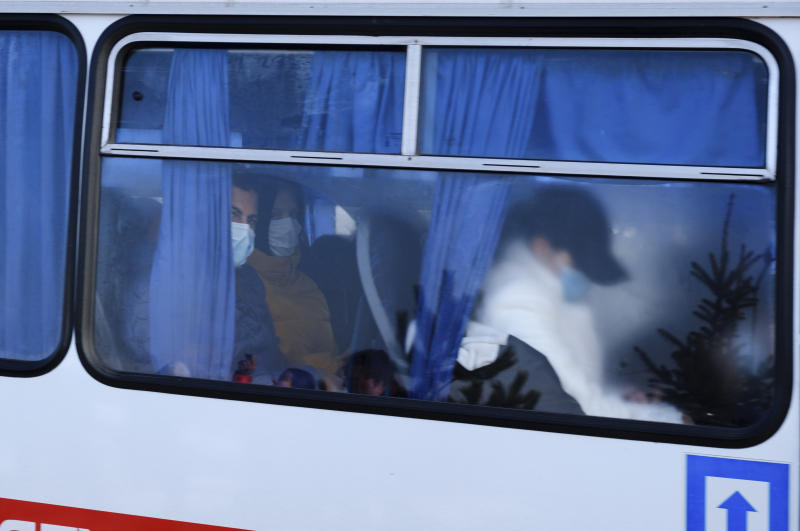 Busses with passengers from the Ukrainian aircraft chartered by the Ukrainian government for evacuation from the Chinese city of Wuhan, leave the the gate upon their landing at airport outside Kharkiv, Ukraine, Thursday, Feb. 20, 2020. Ukraine's effort to evacuate more than 70 people from China due to the outbreak of the new COVID-19 virus was delayed because of bad weather as evacuees travel to a hospital where they are expected to be quarantined. (AP Photo/Igor Chekachkov)