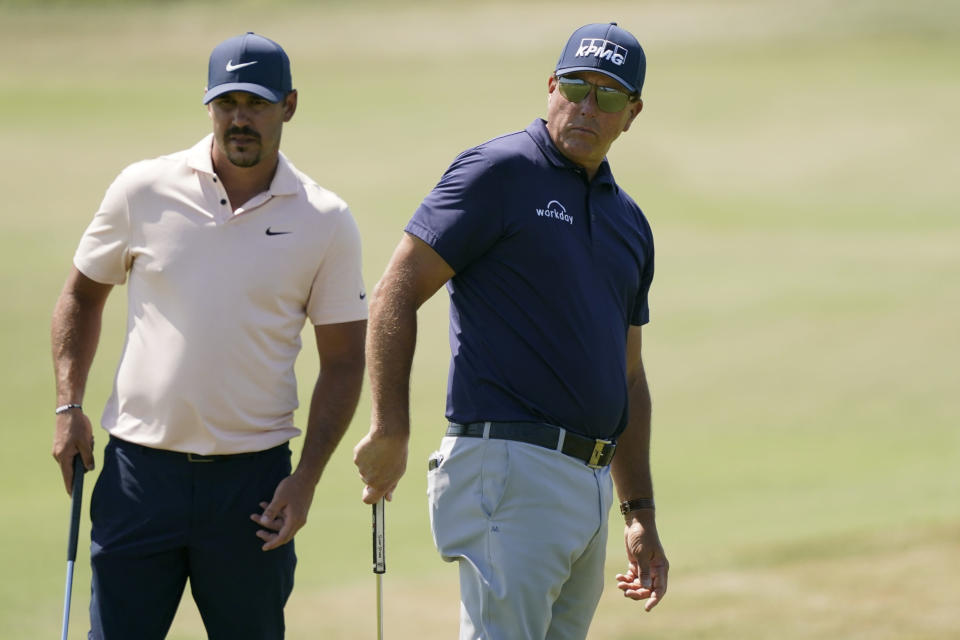 Brooks Koepka, left, and Phil Mickelson watch Mickelson putt on the fourth green during the final round at the PGA Championship golf tournament on the Ocean Course, Sunday, May 23, 2021, in Kiawah Island, S.C. (AP Photo/Matt York)