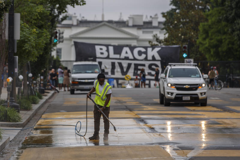 A city worker cleans the words Black Lives Matter painted in bright yellow letters on 16th Street at the site of protests, Wednesday, June 10, 2020, near the White House in Washington. The protests began over the death of George Floyd, a black man who was in police custody in Minneapolis. Floyd died after being restrained by Minneapolis police officers. (AP Photo/Carolyn Kaster)