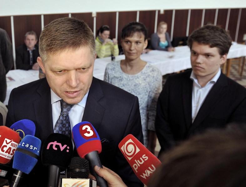 Slovak Prime Minister and presidential candidate Robert Fico, left, speaks to journalists as his wife Svetlana, center, and his son Michal, right, look on after casting their ballots in the second round of the presidential elections in Velke Dvorany, West Slovakia, Saturday, March 29, 2014. (AP Photos,CTK/Jan Koller) SLOVAKIA OUT