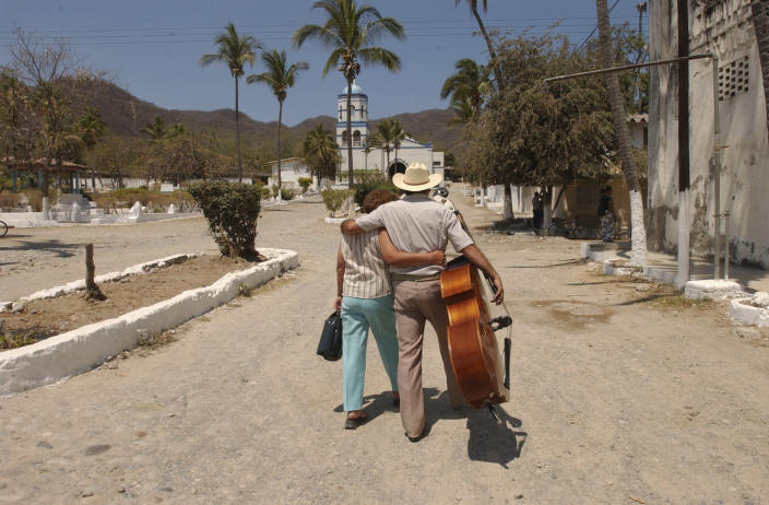 FILE - In this May 12, 2005 file photo, inmate Francisco Loera, who is serving a 10 year sentence, walks with his bass while embracing his partner Alicia Anchondo who arrived to visit him at the Islas Marias federal prison island, located 90 miles south of Mazatlan, Mexico. President Andres Manuel Lopez Obrador said on Monday, Feb. 18, 2019 that he will close the famed island penal colony and will have it converted into a cultural and environmental education center. (AP Photo/Eduardo Verdugo, File)