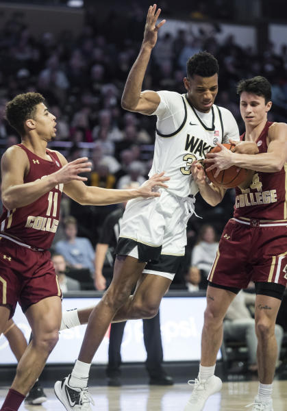 Wake Forest forward Ody Oguama (33) struggles for possession of the ball with Boston College guards Derryck Thornton (11) and Chris Herren Jr. (24) in the first half of a college basketball game Sunday, Jan. 19, 2020, in Winston-Salem, N.C. (Allison Lee Isley/Winston-Salem Journal via AP)
