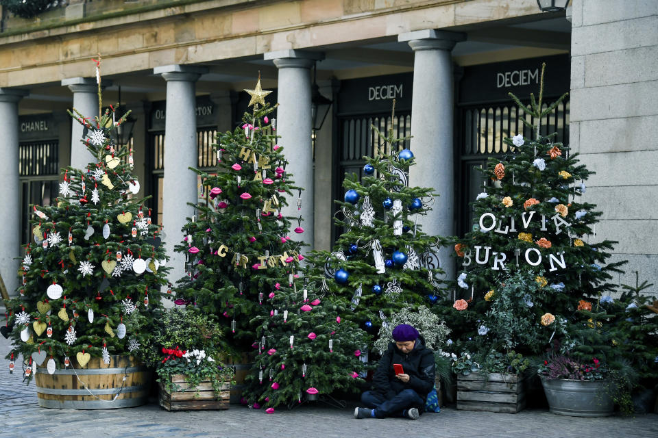 A woman sits amid Christmas trees in Covent Garden, in London, Tuesday, Nov. 24, 2020. Haircuts, shopping trips and visits to the pub will be back on the agenda for millions of people when a four-week lockdown in England comes to an end next week, British Prime Minister Boris Johnson said Monday. (AP Photo/Alberto Pezzali)
