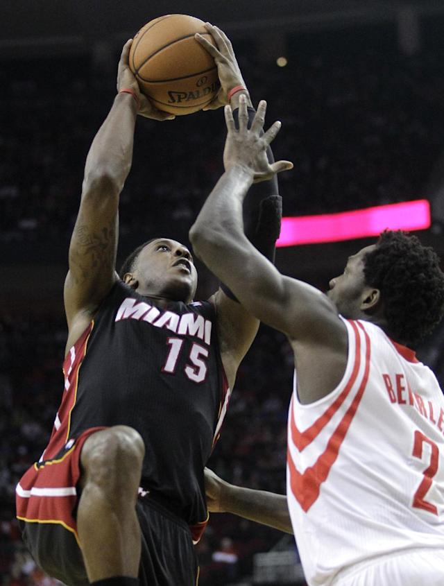 Miami Heat guard Mario Chalmers (15) shoots over Houston Rockets guard Pat Beverly (2) during the first quarter of an NBA basketball game, Tuesday, March 4, 2014, in Houston. (AP Photo/Patric Schneider)