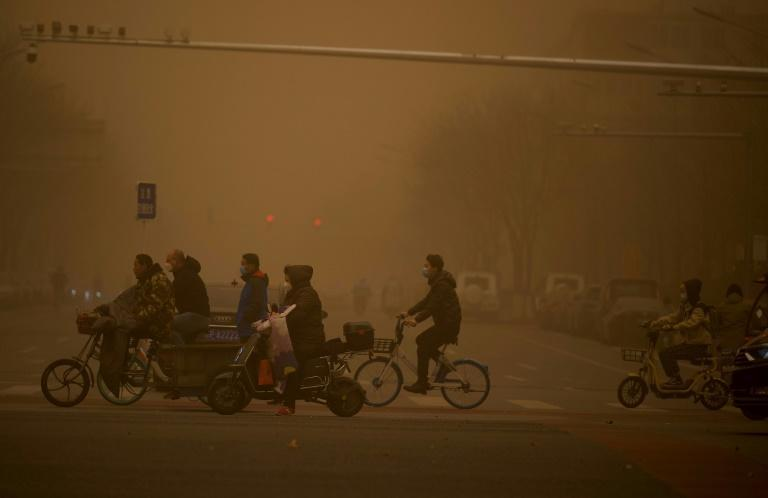 Beijing residents used goggles, masks and hairnets to protect themselves from the choking dust and sand
