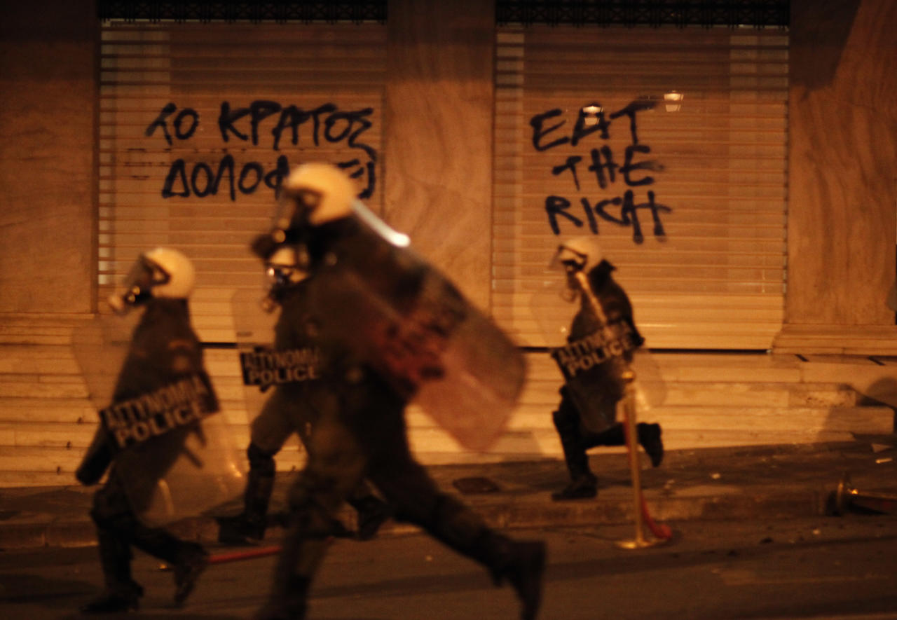 """Riot Policemen chase protesters in front of a hotel during a protest  in Athens, Wednesday April 4 2012. The graffiti reads """"The Nation Murders"""". A Greek retiree shot himself dead in Athens' main square Wednesday, criticizing  politicians over the country's financial crisis in a suicide note that triggered violent clashes hours later between police and anti-austerity protesters. (AP Photo/Kostas Tsironis)"""