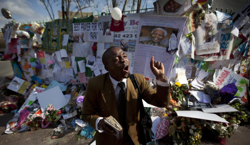 """Gift Mapuka, who describes himself as a """"Global Mission Pioneer"""" from the Seventh-day Adventist Church, preaches about Jesus and Nelson Mandela, in front of a wall of get-well messages and flowers left by well-wishers, outside the entrance to the Mediclinic Heart Hospital where former South African President Nelson Mandela is being treated in Pretoria, South Africa, Friday, July 5, 2013. (AP Photo/Ben Curtis)"""