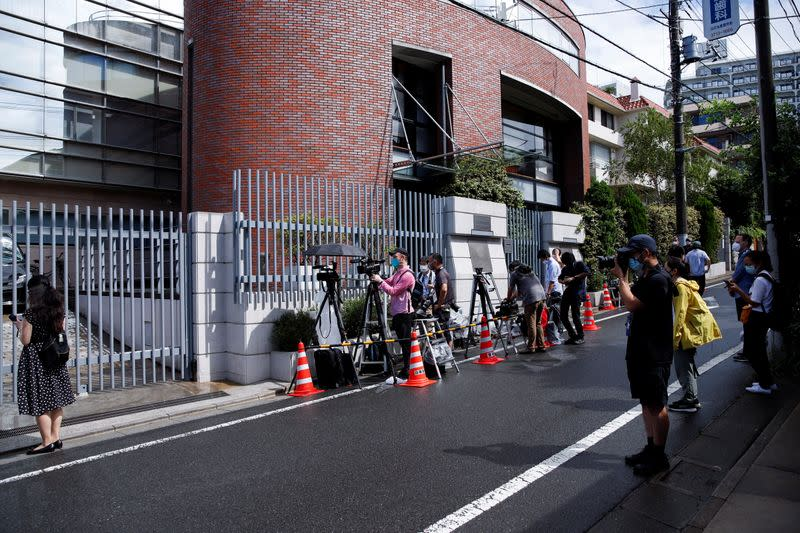 Members of the media stand in front of the Polish Embassy in Tokyo