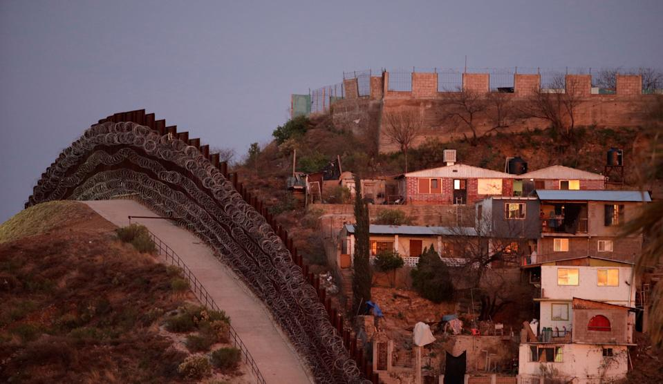 A razor-wire-covered border wall separates Nogalas, Mexico, at right, and Nogales, Ariz. at dusk Saturday, March 2, 2019. (AP Photo/Charlie Riedel)
