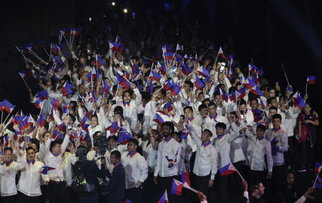 Philippine delegates wave flags during the opening ceremony of the 30th South East Asian Games at the Philippine Arena, Bulacan province, northern Philippines on Saturday, Nov. 30, 2019. (AP Photo/Aaron Favila)