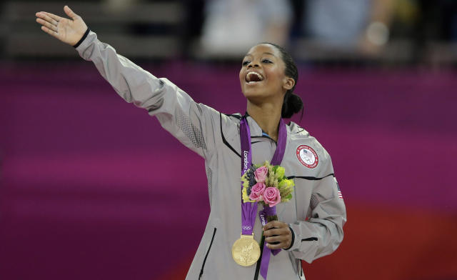 ALTERNATE CROP OF OGYM222- U.S. gymnast Gabrielle Douglas acknowledges the crowd after receiving her gold medal during the artistic gymnastics women's individual all-around competition at the 2012 Summer Olympics, Thursday, Aug. 2, 2012, in London. (AP Photo/Gregory Bull)