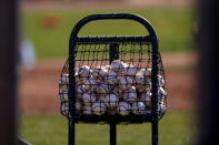 Baseballs sit in a basket at the Seattle Mariners' spring training, Thursday, Feb. 25, 2021, in Peoria, Ariz. (AP Photo/Charlie Riedel)