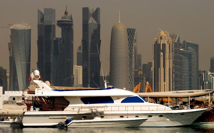 A boat moored with the Qatari capital Doha skyline in the background (AFP Photo/Patrick Baz)