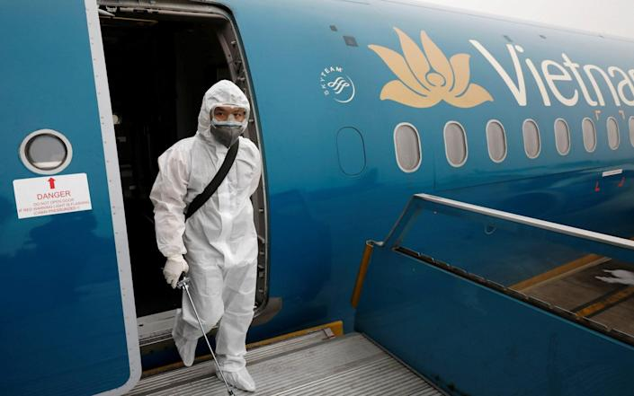A health worker sprays disinfectant inside an Vietnam Airlines plane, the employer of the British pilot who is now in intensive care in Vietnam - Reuters