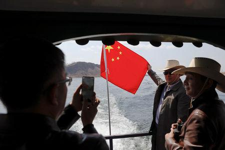 Tourists pose with Chinese flag on a boat taking them from the Chinese side of the Yalu River for sightseeing close to the the shores of North Korea, near Dandong, China's Liaoning province, April 1, 2017. REUTERS/Damir Sagolj
