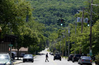 A man walks across the street in Ellenville, N.Y., Wednesday, June 16, 2021. Less than 100 miles north of New York City, Ulster County is popular destination for weekenders headed to Woodstock or the Catskill Mountains. Though pretty, there are pockets of poverty. The county is working with the Center for Guaranteed Income Research at the University of Pennsylvania on a pilot program funded by private donations. One hundred households making less than $46,900 a year in May began receiving a $500 payment each month for a year. Recipients of the money can spend it as they wish, but will be asked to participate in periodic surveys about their physical health, mental health and employment status. (AP Photo/Seth Wenig)