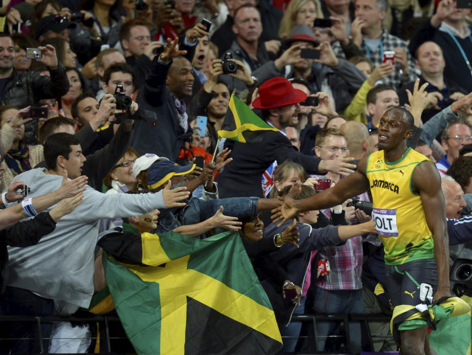 Usain Bolt celebrates with the crowd, shaking hands of fans and taking pictures. (Thomas Lohnes/AP Photo)