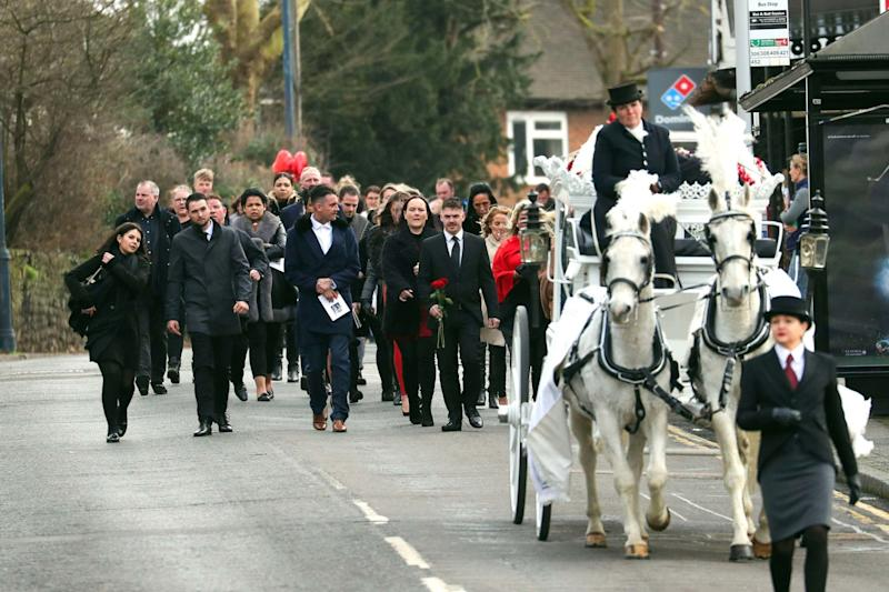 Mourners walk behind the horsedrawn carriages carrying Joey and Billy Smith (PA)