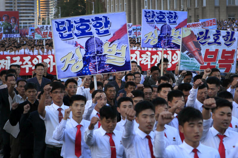 """DELETES NUMBER OF PEOPLE - North Koreans gather at Kim Il Sung Square to attend a mass rally against America on Saturday, Sept. 23, 2017, in Pyongyang, North Korea, a day after the country's leader issued a rare statement attacking Donald Trump. The sign on the left foreground reads """"decisive punishment"""" while the sign on the right reads """"decisive revenge."""" (AP Photo/Jon Chol Jin)"""