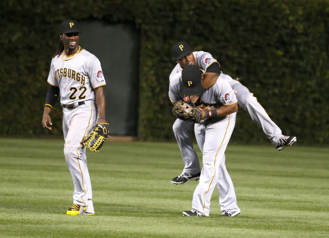 Pittsburgh Pirates center fielder Andrew McCutchen, left, Starling Marte, center and Marlon Byrd celebrate the Pirates' 2-1 win over the Chicago Cubs after a baseball game Monday, Sept. 23, 2013, in Chicago. (AP Photo/Charles Rex Arbogast)