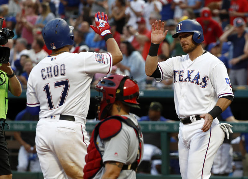Texas Rangers' Shin-Soo Choo, left, and Jeff Mathis, right, celebrate Choo's two-run home run that scored Mathis as St. Louis Cardinals catcher Yadier Molina, kneels by the plate in the second inning of a baseball game in Arlington, Texas, Friday, May 17, 2019. (AP Photo/Tony Gutierrez)